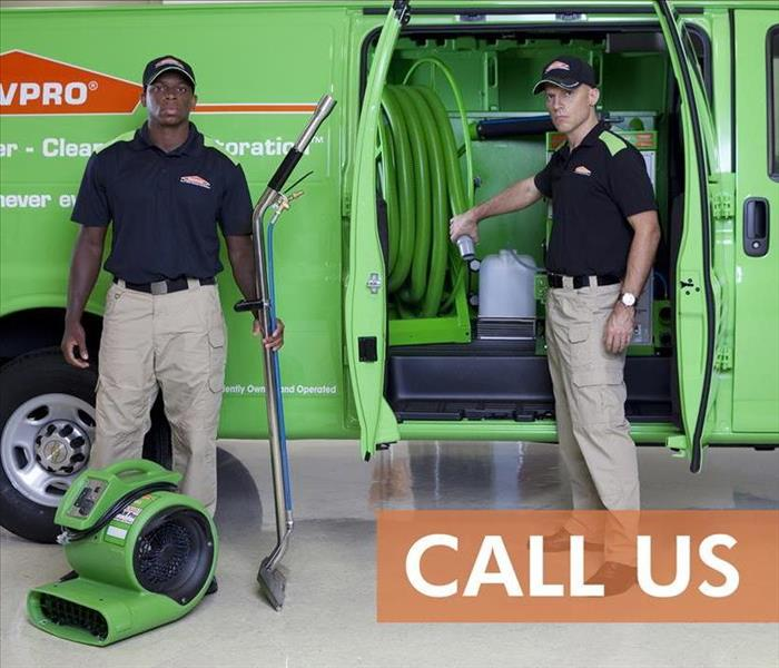 Two SERVPRO technicians in front on a van with drying equipment.